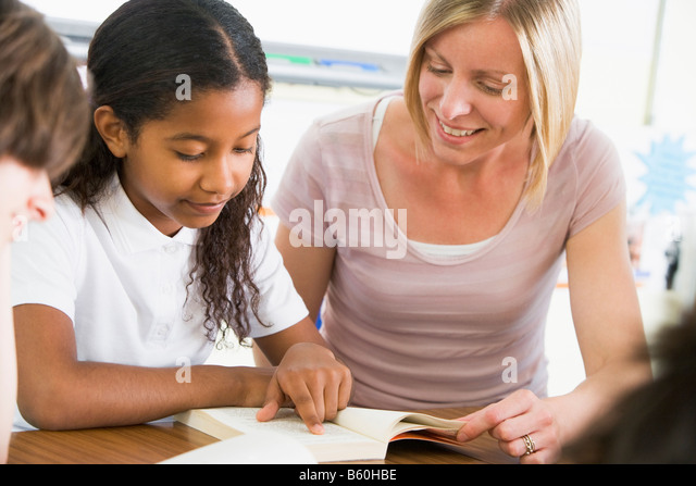 Student in class reading book with teacher - Stock Image