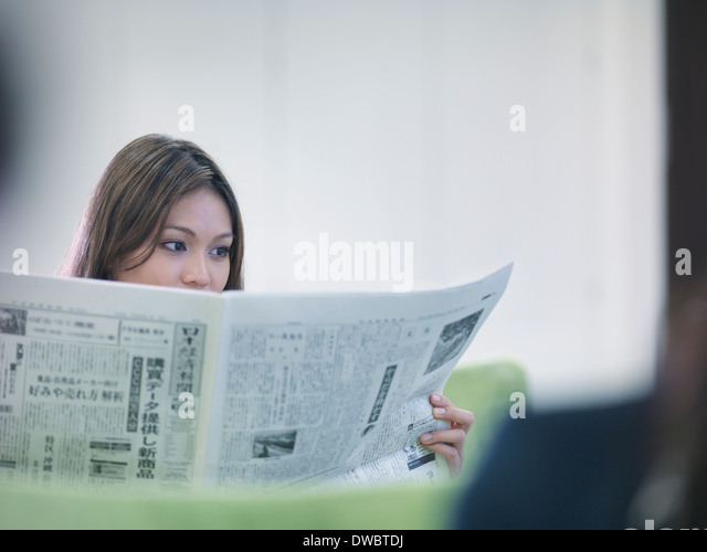 Businesswoman reading Japanese newspaper - Stock Image