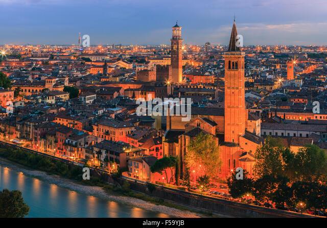 Santa Anastasia church and Torre dei Lamberti at dusk along the Adige river in Verona, Italy. - Stock Image