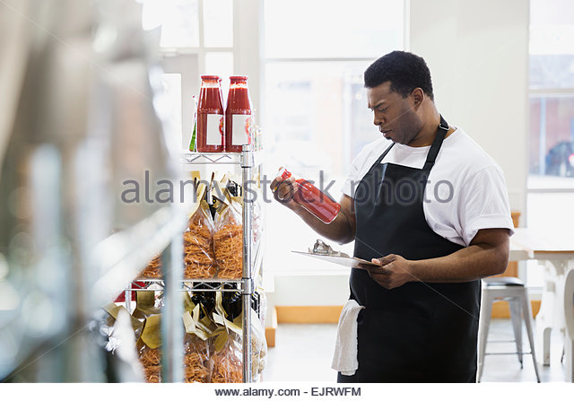 Worker taking inventory with clipboard in grocery store - Stock Image