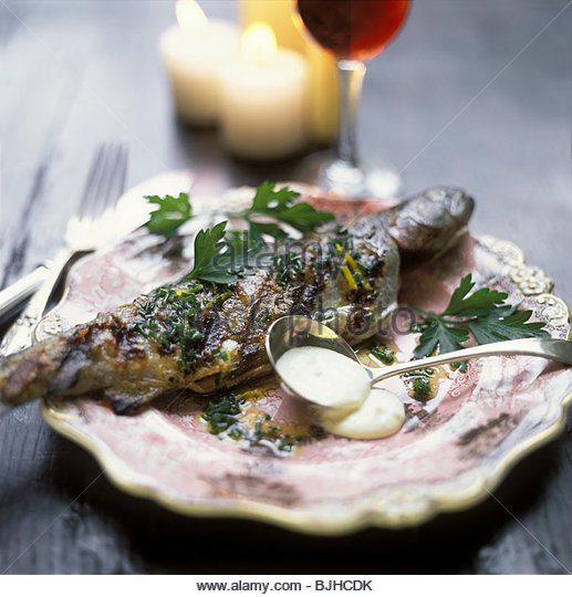 Fried trout with cream sauce on a fine plate (2) - Stock Image