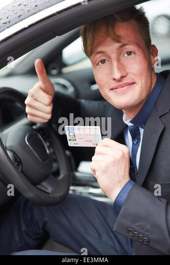 Young happy man in car holding his new drivers license and his thumbs up - Stock Image
