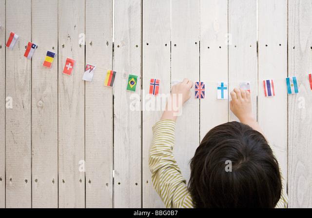 A boy reaching flags - Stock-Bilder