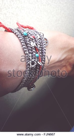 Cropped Image Of Person Wearing String Bracelet - Stock Image