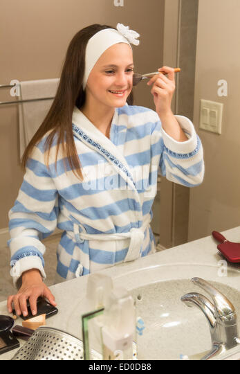 Young girl (12-13) looking in mirror while applying makeup - Stock Image