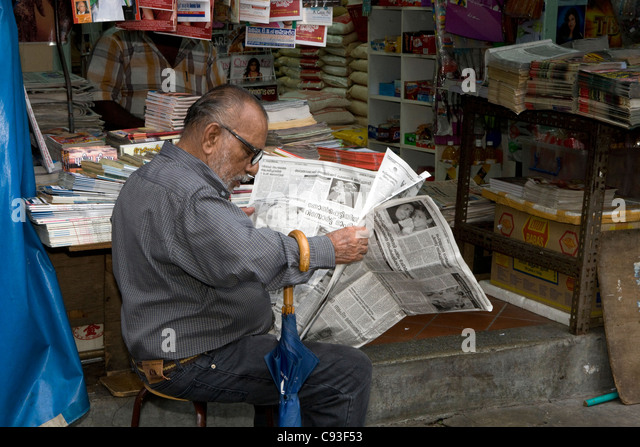 Little India: man with newspaper - Stock Image