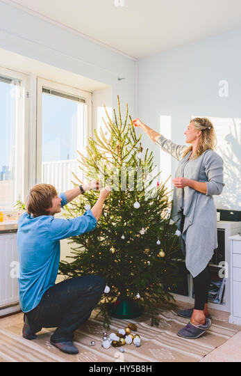 Finland, Helsinki, Couple decorating christmas tree together - Stock Image