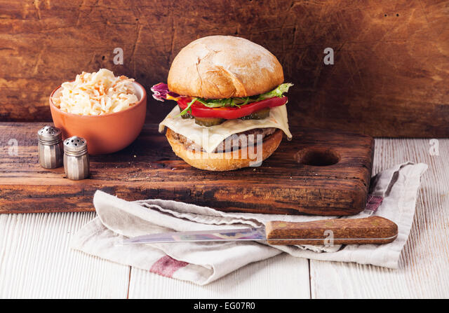Burger with meat and coleslaw on wooden background - Stock Image