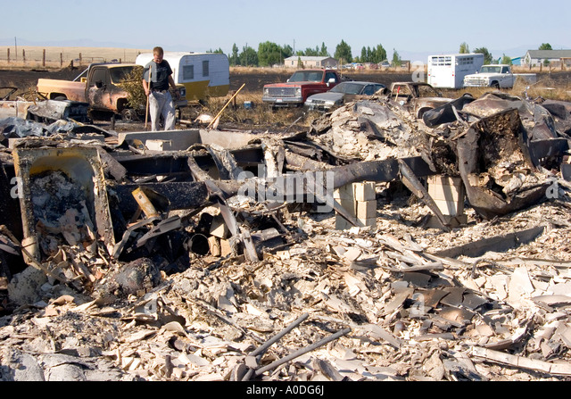 Victims sift through the rubble of a home destroyed by wildfire near Mountain Home Idaho - Stock-Bilder