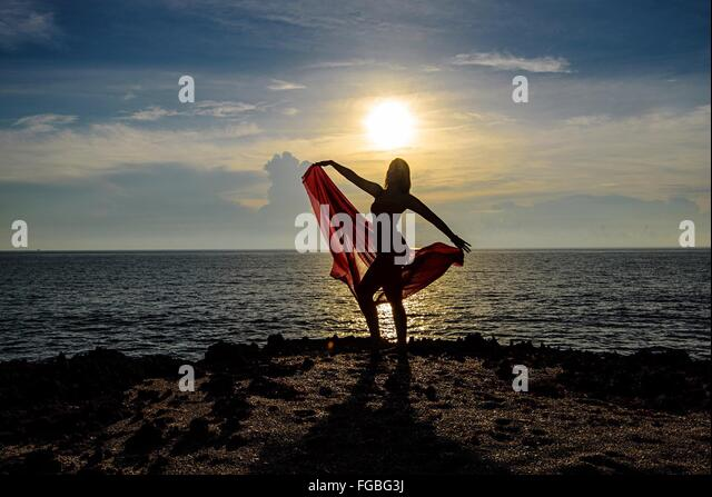 Woman Dancing On Cliff By Sea Against Sky During Sunset - Stock Image