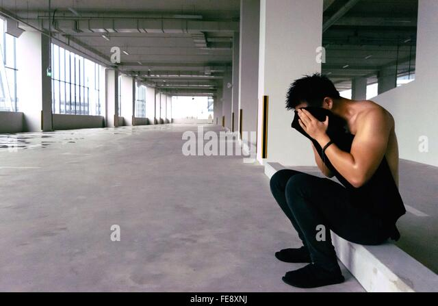 Side View Of Man Covering His Face With T-Shirt - Stock Image