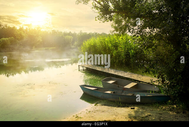 Boats near pier at beautiful summer morning - Stock Image