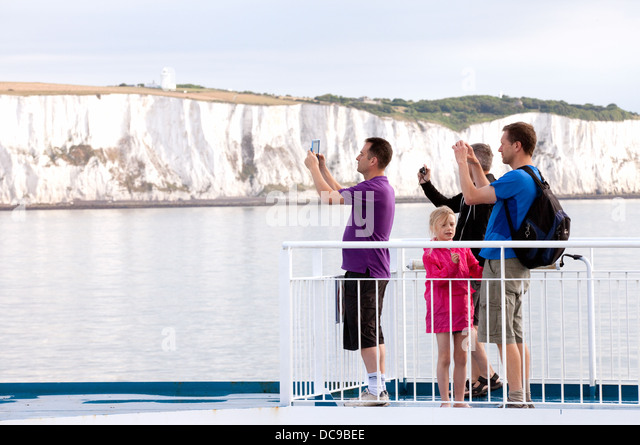 Cross channel car ferry passengers taking photos of the White cliffs of Dover as they travel to France on holiday - Stock-Bilder