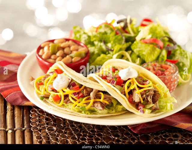 Two soft carnitas tacos served with side salad and pinto beans - Stock Image