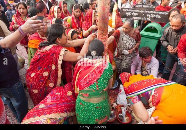 Women apply a string to the chir during Holi festival celebrations, Kathmandu, Nepal - Stock Image