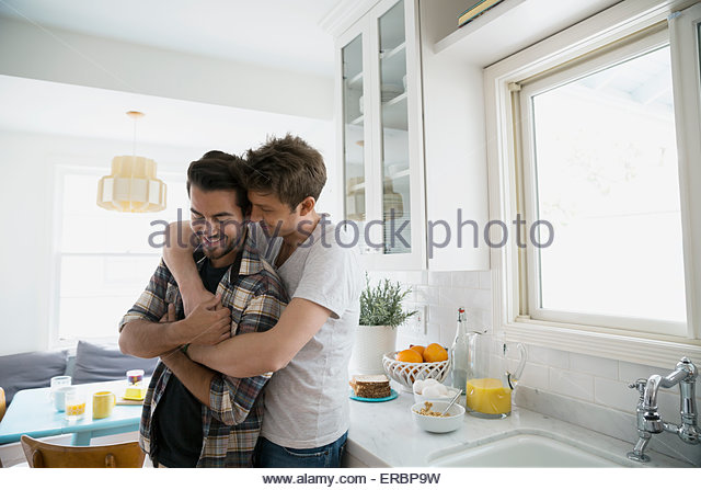 Affectionate homosexual couple hugging in kitchen - Stock Image