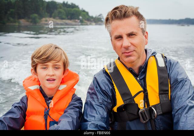 Sweden, Uppland, Runmaro, Barrskar, Father and son (6-7) on motorboat - Stock Image
