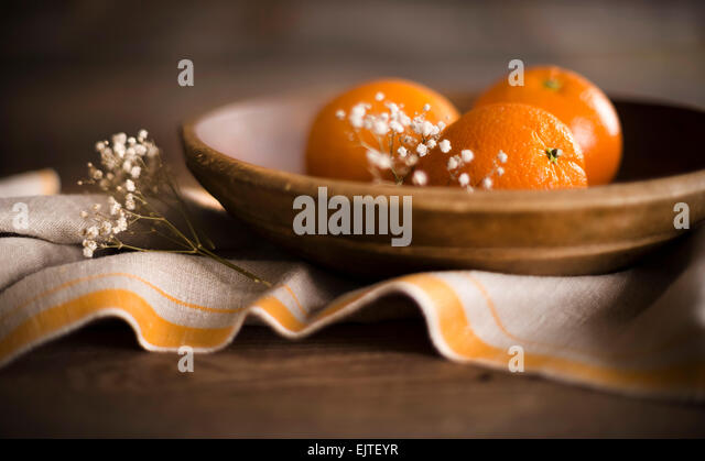 3 ripe oranges in a rustic wooden bowl with linen and flowers. - Stock Image