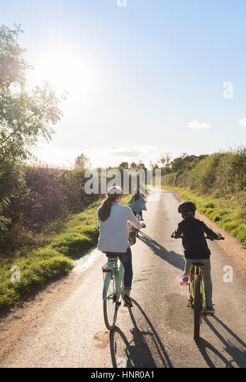 A family bike ride with mother and two children in the countryside. - Stock Image