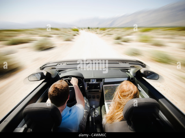 USA, California, Palm Springs, Coachella Valley, San Gorgonio Pass, Couple driving through desert in convertible - Stock-Bilder