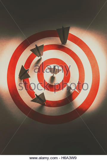 Business still life photo on pin board paper plane making hits and misses into a target sign. Pin point your target - Stock Image