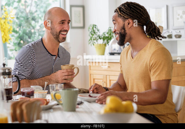 Smiley homosexual couple having breakfast in kitchen - Stock-Bilder