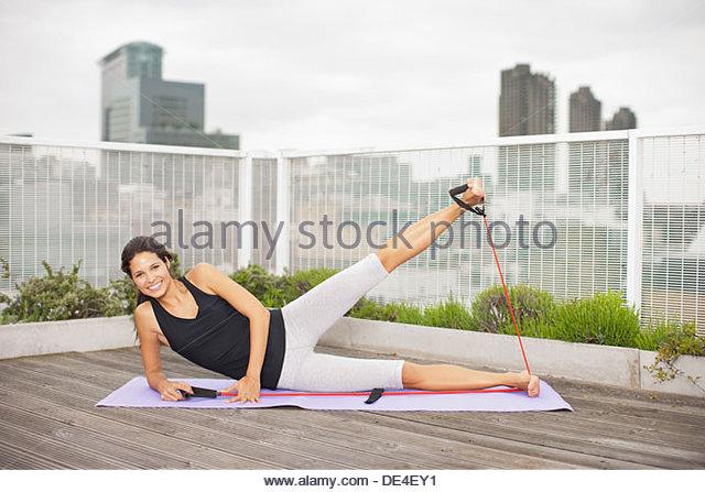 Woman exercising on rooftop deck - Stock-Bilder
