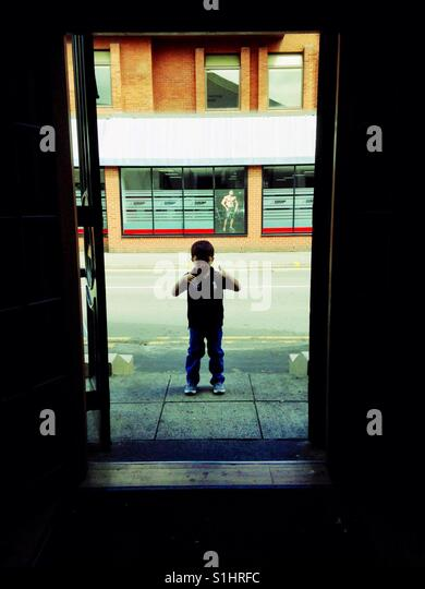 A young boy in silhouette in a doorway. - Stock Image