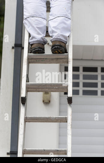 A painter and decorator stands on a ladder to paint the exterior wall of a house. - Stock Image