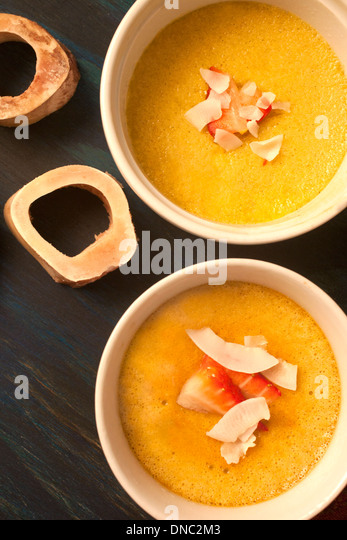 Yellow custard in white souffle dishes overhead - Stock Image