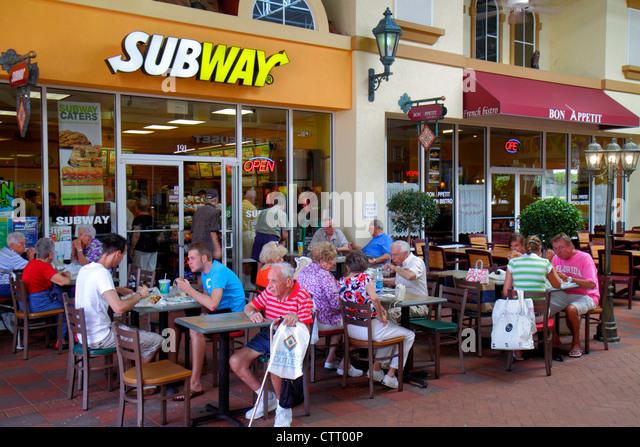 Florida Estero Miromar Outlets shopping dining Subway sandwich shop alfresco senior man - Stock Image