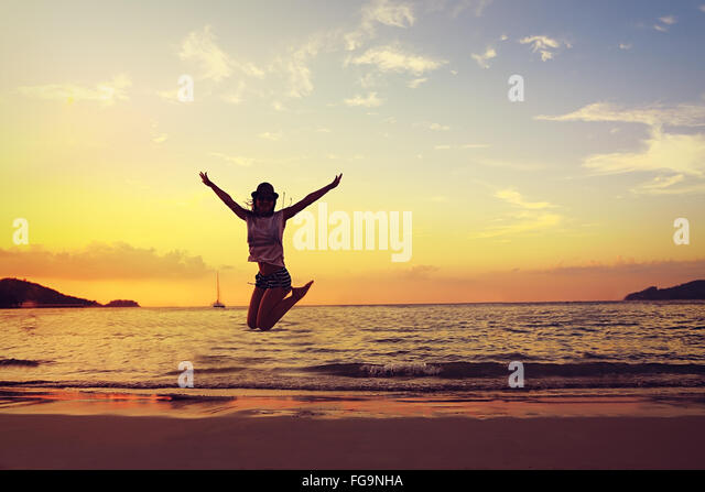 Beautiful energy young woman silhouette jumping on beautiful sunset bright background - Stock Image
