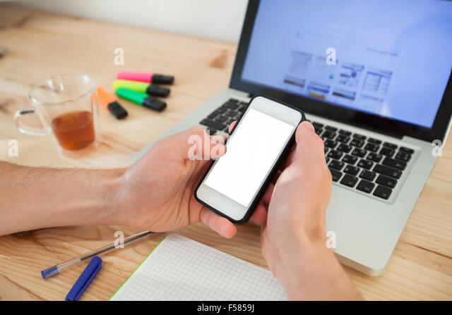 man using smartphone with white screen near laptop in home interior - Stock Image