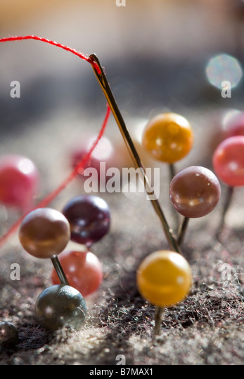 Pins and handsewing needle with thread - Stock Image