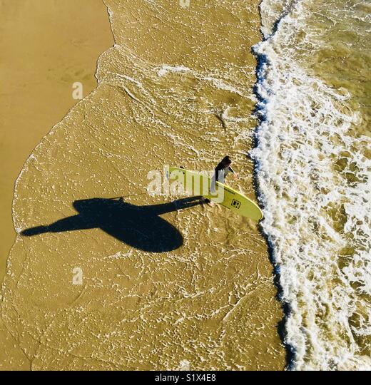 A female surfer walks out to the surf. Manhattan Beach, California USA. - Stock Image