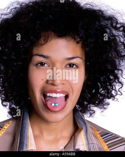 Young Woman With Curly Hair Taking Pill - Stock Image