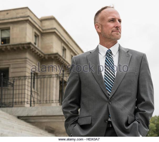 Pensive Caucasian businessman standing outdoors - Stock Image
