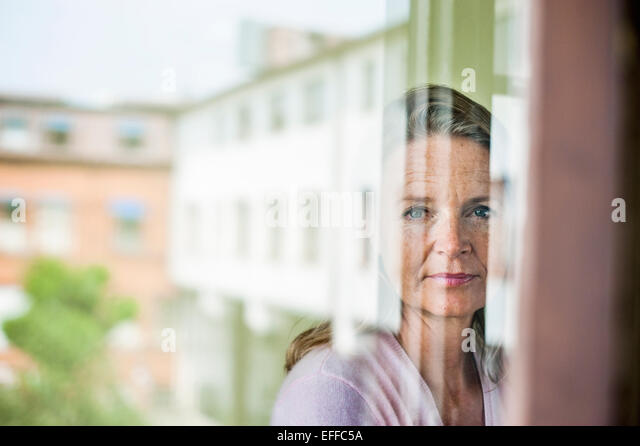 Mature teacher looking outside window with reflection of school building on glass - Stock Image