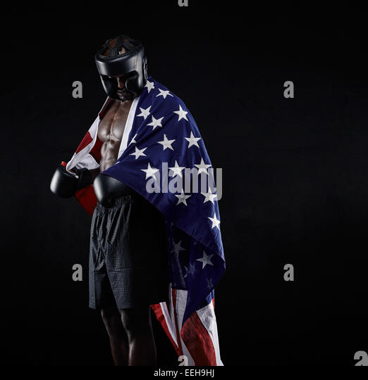 Portrait of african american Boxer with the American flag draped around his body against black background - Stock Image
