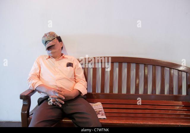 Nicaragua Managua Avenida Simon Bolivar Plaza Inter shopping mall bench public area Hispanic man resting sleeping - Stock Image
