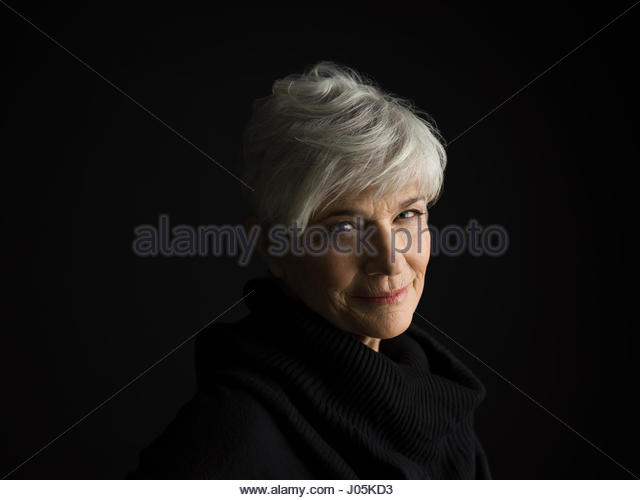 Portrait smiling senior woman with short gray hair against black background - Stock Image