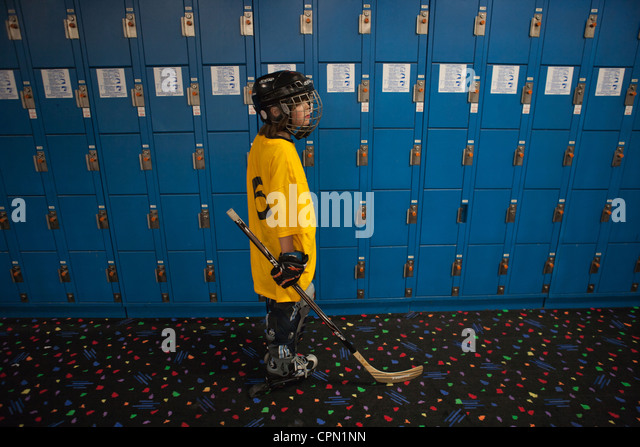 Nine year old boy standing in front of lockers, getting ready to play hockey. - Stock Image