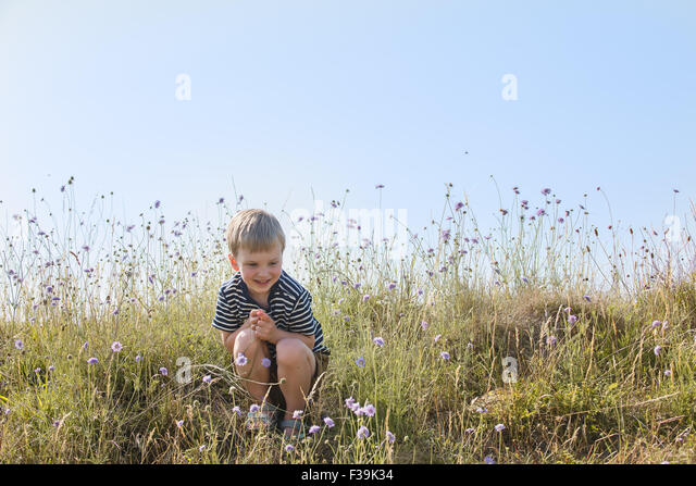 Boy sitting in green field, smiling - Stock Image