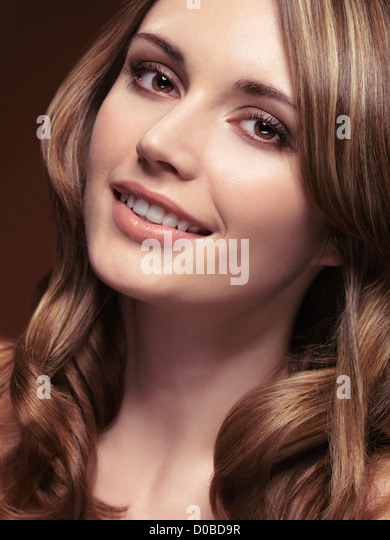Beauty portrait of a smiling young woman with beautiful brown hair and highlights - Stock Image