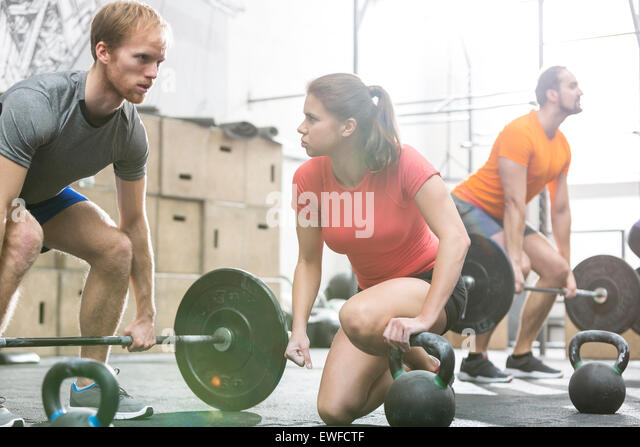 People weightlifting in crossfit gym - Stock Image
