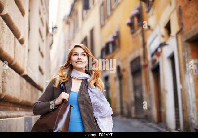 Young woman strolling down street, Rome, Italy - Stock Image