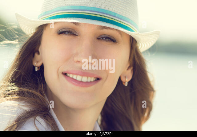 Young smiling hipster woman has fun near sea at summer vacation. Warm color toned image - Stock-Bilder