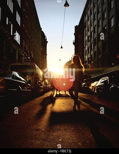 Portrait Of Woman Standing On City Street Between Buildings During Sunset - Stock-Bilder