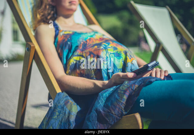 A pregnant woman is relaxing in a deck chair and is using her smart phone - Stock Image