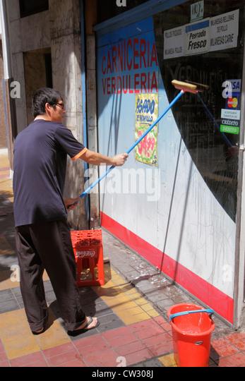 Argentina Mendoza Avenida San Juan sidewalk butcher shop business produce Asian man grocer storefront window washing - Stock Image